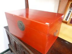 A CHINESE TWO HANDLED RED LACQUER COFFER WITH BRASS CIRCULAR LOCK PLATE. 77.5 x 49 x H.39.5cms.