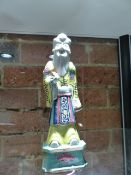A CHINESE PORCELAIN FIGURE OF SHOULAO STANDING WEARING A YELLOW GROUND ROBE AND HOLDING A PEACH. H.