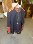 A VINTAGE BANDSMAN'S BLACK TUNIC WITH CRIMSON COLLAR AND CUFFS TOGETHER WITH A VINTAGE DISPLAY