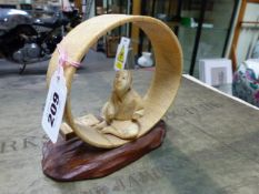 A JAPANESE IVORY FIGURE SEATED WITHIN AN UNFINISHED COOPERED TUB ON IT'S SIDE. H.12cms.