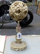 A CHINESE IVORY PUZZLE BALL CARVING WITH STAND HAVING A ROTATING RETICULATED KNOP AND A FURTHER