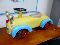 A VINTAGE STYLE TIN PLATE CHILD'S RIDE-ON TOY CAR WITH EYE HEADLAMPS. L.74cms.