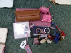 TWO TINY RADLEY PURSES, FIVE KEY RINGS/ RADLEY CHARMS, A BOOKMARK AND A SPECTACLES CASE.