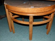 A G-PLAN GLASS TOPPED COFFEE TABLE WITH THREE NESTING TABLES BENEATH. Dia.80cms.