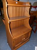 AN ERCOL PALE ELM WATERFALL BOOKCASE WITH CUPBOARD BASE. 61 x 34 x H.101cms.