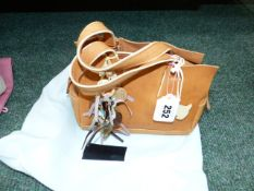A RADLEY SMALL GRAB BAG IN LIGHT TAN LEATHER WITH TWO CHARMS AND DUST COVER.