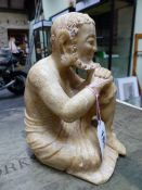 AN ORIENTAL ALABASTER FIGURE OF A BEARDED MONK SEATED WITH HIS CHIN RESTING ON HAND FOLDED ON A