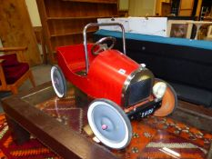 A VINTAGE STYLE RED PAINTED TIN PLATE PEDAL CAR. L.83cms.