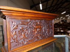 AN OAK PANEL CARVED WITH A MASK AMONGST FOLIAGE AND SET INTO A BOX FORM WITH THE NARROW ENDS OPEN.