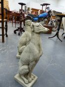 A PAIR OF COMPOSITE STONE FIGURES OF SEATED GREYHOUNDS. H.54cms.