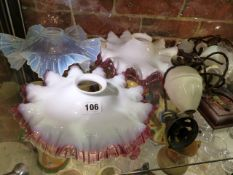 A PAIR OF CRANBERRY EDGED MILK GLASS SHADES, ANOTHER IN VASELINE GLASS. Dia.25cms TOGETHER WITH