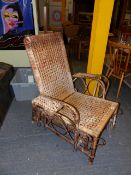 AN ANTIQUE DRYAD TYPE RATTAN RECLINING TERRACE CHAIR WITH PULL OUT FOOTREST.
