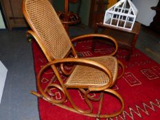 AN ANTIQUE BENTWOOD THONET STYLE ROCKING CHAIR WITH CANE BACK AND SEAT.