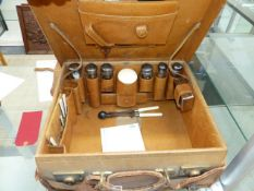 A VINTAGE LEATHER LADIES TRAVELLING CASE BY S.FISHER, LONDON CONTAINING SILVER TOPPED BOTTLES,ETC