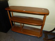 AN ERCOL PALE ELM THREE TIER STAND ON CASTORS. W.91 x H.71cms.