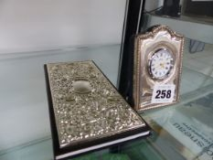 A SILVER CASED DESK CLOCK AND A NOTEPAD.