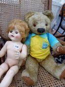A TEDDY BEAR AND A DOLL.