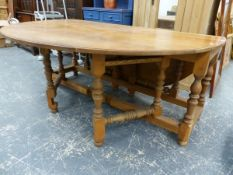 A VERY LARGE OAK DROP LEAF DINING TABLE.