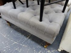 A BUTTON UPHOLSTERED FOOTSTOOL.