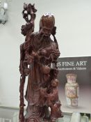 A CARVED WOODEN ORIENTAL FIGURE.