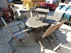 A TEAK FOLDING PATIO TABLE AND CHAIRS
