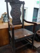 A VICTORIAN CARVED OAK ARMCHAIR.