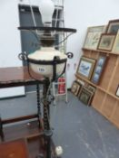 A WROUGHT IRON STANDARD LAMP.