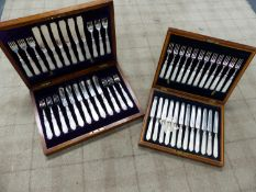 TWO CASED SETS OF SILVER HALLMARKED AND MOTHER OF PEARL CUTLERY.