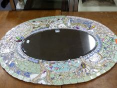A BEVELLED GLASS OVAL MIRROR IN A FRAME OF MOSAIC CERAMICS FRAGMENTS, MIRRORED GLASS AND