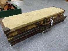A BRASS CORNERED LEATHER SHOTGUN CASE TOGETHER WITH A WILLIAM EVANS CANVAS COVERED OAK CASE, THE RED