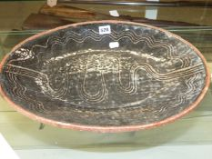AN ABUJA OVAL PLATTER THE DEEP BROWN GLAZE RAKED WITH FOUR WAVY LINES AROUND THE RIM AND