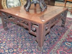 A CHINESE HARDWOOD LOW TABLE WITH PIERCED FRIEZE ON SQUARE LEGS AND CARVED SCROLL FEET. 76 x 76 x