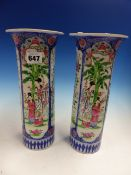 A PAIR OF JAPANESE FAMILLE ROSE SLEEVE VASES PAINTED WITH BLUE FRAMED PANELS OF LADIES AND