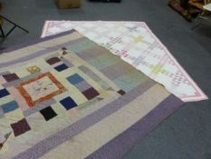 TWO PATCHWORK QUILTS, ONE WITH PINK BORDERED GEOMETRIC PATTERNS. 219 X 206cms. THE OTHER WITH