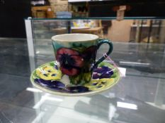 A WILLIAM MOORCROFT PANSY PATTERN COFFEE CUP AND SAUCER
