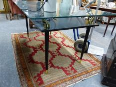 A MID CENTURY GLASS TOPPED TABLE WITH EBONISED AND BRASS SWAN HEAD SUPPORTS OVER A HIGH UNDERTIER