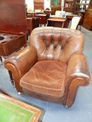 A PAIR OF ART DECO BUTTON BACK LEATHER CLUB ARMCHAIRS ON TURNED BUN FEET WITH BRASS CASTERS. (2)