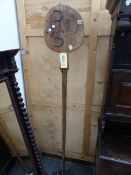 AN ANTIQUE BREAD PADDLE MOUNTED STANDING ON IRON BASE.