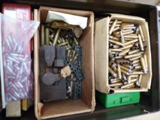 A COLLECTION OF BRASS RIFLE AND PISTOL CALIBRE BRASS CASES, A PAIR OF EARLY EAR PROTECTORS AND ALLOY