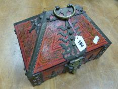 AN INDIAN BRASS BOUND RED GROUND WOODEN BOX, A BRASS HANDLE AT THE APEX OF THE ROOF SHAPED HINGED