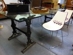 A PAIR OF VICTORIAN CAST IRON TRESTLE STANDS SUPPORTING A LARGE PLATE GLASS DINING TABLE TOP. 95 x