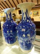 A PAIR OF JAPANESE BLUE AND WHITE BALUSTER VASES PAINTED WITH MOUNTAINOUS ISLAND LANDSCAPES. H