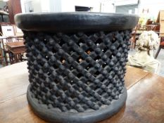 A BAMILEKE TRIBAL EBONISED CYLINDRICAL SPIDER STOOL, THE SIDES PIERCED AND CARVED WITH BOSSES AND