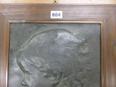 AN EARLY 20th.C. BRONZED PLASTER PROFILE OF A CHILD IN WOODEN FRAME, MONOGRAMMED F C. 41 x 31.5cms.