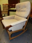 A MID CENTURY TEAK FRAME ARMCHAIR TOGETHER WITH A MATCHING ROCKING CHAIR. (2)
