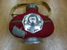 AN EASTERN ALUMINIUM DRINKING FLASK DECORATED WITH A BOSS ON ONE OF THE RED BAIZE COVERED SIDES. H