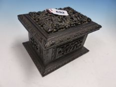 A CHINESE EBONY BOX CARVED IN RELIEF WITH FIGURES IN LEAFY VILLAGES, THE HINGED RECTANGULAR LID