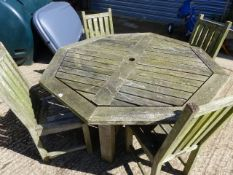AN OCTAGONAL TEAK GARDEN TABLE AND FOUR CHAIRS.