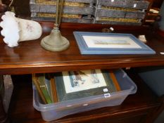 A COLLECTION OF PRINTS AND A TABLE LAMP.