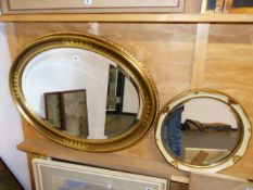 A LARGE OVAL GILT FRAMED MIRROR AND A SMALLER MIRROR.